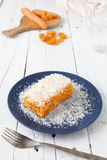 Delicious carrot and coconut cake. Piece of carrot and coconut cake with some layers of cookies, covered with grated coconut in a blue plate on a white weathered Stock Photo