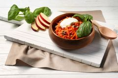 Delicious carrot raisin salad with sour cream in brown clay bowl Stock Photos