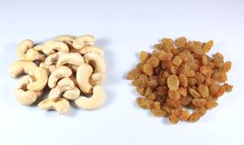 Delicious cashew nuts and dry grapes. Piles of delicious cashew nuts and dry grapes on white background stock photography