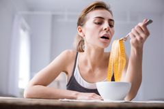 Cheerless young woman pretending to eat. So delicious. Cheerless young woman sitting at the table while pretending to eat a centimeter tape Stock Image
