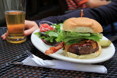 Delicious cheesburger,side salad and cold beer. Delicious cheeseburger piled high with bacon,lettuce and fresh sliced tomato,with cold glass of beer on the side Stock Photos