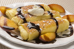 Delicious Cheese Blintzes in Closeup. Traditional Jewish food cheese blitzes with whipped cream, peaches and chocolate sauce in closeup Stock Photos