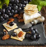Delicious cheese crackers appetizer with grapes and pecans Royalty Free Stock Images