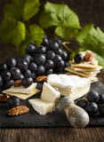 Delicious cheese crackers appetizer with grapes and pecans. Royalty Free Stock Photography