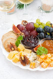 Delicious cheese and fruit plate to the holiday on table Stock Photos