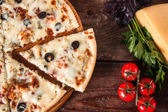 Delicious cheese pizza. Traditional italian food. Fresh baked italian pizza with olives and cheese, cut slice on wooden table with ingredients, flat lay Stock Photo