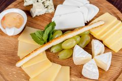 Delicious cheese plate or cheese platter from several types of cheese with honey and fruit. For creative work in cooking stock images
