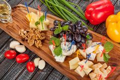 Delicious cheese plate or cheese platter from several types of cheese with honey and fruit. For creative work in cooking royalty free stock photography