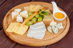 Delicious cheese plate or cheese platter from several types of cheese with honey and fruit. For creative work in cooking stock photo