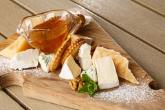 Tasting cheese dish on a wooden plate. Food for wine and romantic, cheese delicatessen on a wooden rustic table. Top royalty free stock photo