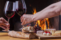 Delicious cheese and wine at the fireplace Royalty Free Stock Image