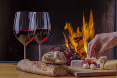 Delicious cheese and wine at the fireplace Royalty Free Stock Images