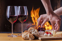 Delicious cheese and wine at the fireplace Stock Images