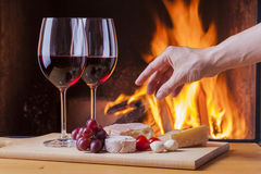 Delicious cheese and wine at the fireplace Royalty Free Stock Photography