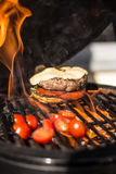 Delicious cheeseburger with tomatoes cooking on hot flaming grill. Barbecue. Restaurant Royalty Free Stock Photography