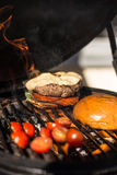 Delicious cheeseburger with tomatoes cooking on hot flaming grill. Barbecue. Restaurant Royalty Free Stock Images