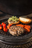 Delicious cheeseburger with tomatoes cooking on hot flaming grill. Barbecue. Restaurant Stock Photography
