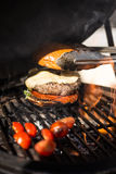 Delicious cheeseburger with tomatoes cooking on hot flaming grill. Barbecue. Restaurant Royalty Free Stock Image