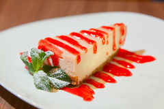 Delicious cheesecake with strawberries and mint on  plate. Delicious cheesecake with strawberries and mint on a plate Royalty Free Stock Images