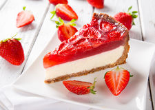 Delicious cheesecake with strawberries on wooden table. Stock Images