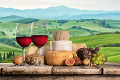 Delicious cheeses with wine on old wooden table. Royalty Free Stock Image