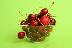 Delicious Cherries in a Bowl. Cherries in a bowl photographed on a green background Stock Photography