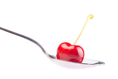 Cherry on a spoon Stock Images