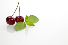 Delicious cherry. Pair with mint leaf on white background Stock Photo