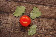 delicious cherry tomatoes sprinkled with salt on a wooden background stock photo