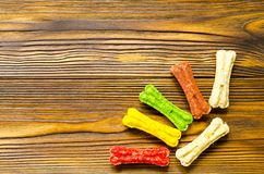 Delicious chewing colored bones for dogs with different tastes o. N wooden background with copy space Royalty Free Stock Photos