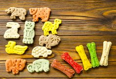Delicious chewing colored bones and zoological biscuits  for dog. S with different tastes on wooden background Royalty Free Stock Photos