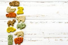 Delicious chewing colored bones and zoological biscuits  for dog. S with different tastes on white wooden background Royalty Free Stock Photo