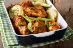 Delicious chicken baked with fennel bulbs in a baking dish close. Up on a table. horizontal Royalty Free Stock Images