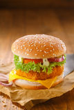 Delicious chicken burger. With a golden crumbed patty and salad ingredients on grungy crumpled brown paper against a wooden backdrop with copyspace stock image