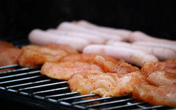 Delicious chicken meat and sausages on grill. Photo of delicious chicken meat and sausages on grill royalty free stock photography