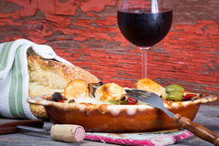 Delicious chicken stew with sesame bread and wine. Delicious chicken stew with sesame bread and a glass of red wine against a grungy wooden backdrop with peeling Stock Image