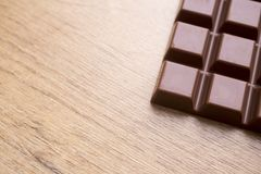 Delicious chocolate bar on wooden table. Detail of delicious chocolate bar on wooden table Royalty Free Stock Photo
