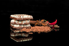 Delicious chocolate bars. Delicious chocolate candy arranged on black background with cocao powder, cinnamon, coffee beans and chilli royalty free stock photos