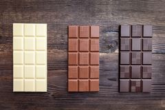 Delicious chocolate bars on wooden background Royalty Free Stock Image
