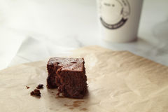 Delicious chocolate brownie with take away coffee in background Stock Photography
