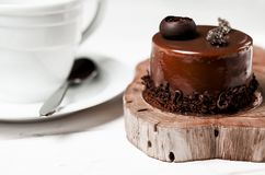 A delicious chocolate cake with chocolate pieces lies on a wooden stand next to a white cup, which stands on a white table stock images