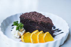 Delicious Chocolate cake decorated with orange on white dish. cl Royalty Free Stock Image