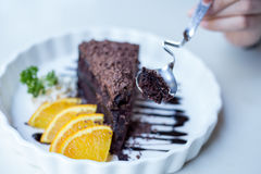 Delicious Chocolate cake decorated with orange on white dish. cl Royalty Free Stock Photo