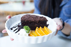 Delicious Chocolate cake decorated with orange on white dish. cl Royalty Free Stock Photos