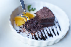 Delicious Chocolate cake decorated with orange on white dish. cl Stock Photos