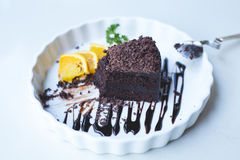 Delicious Chocolate cake decorated with orange on white dish. cl Royalty Free Stock Photography