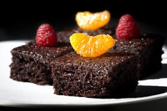 Delicious chocolate cake decorated with raspberries and tangerine. Stock Photo