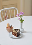 Delicious chocolate cake and dessert near with flowers on white table in cafe Royalty Free Stock Photography