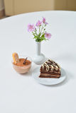 Delicious chocolate cake and dessert near with flowers on white table in cafe Royalty Free Stock Image