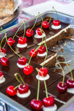 Delicious chocolate cake with fresh cherries. Tasty pastry on a platter Stock Photos